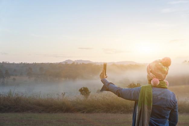 女性観光客は夏の霧の深い朝、屋外のキャンプの冒険の概念で劇的な日の出の間にスマートフォンで写真を撮る