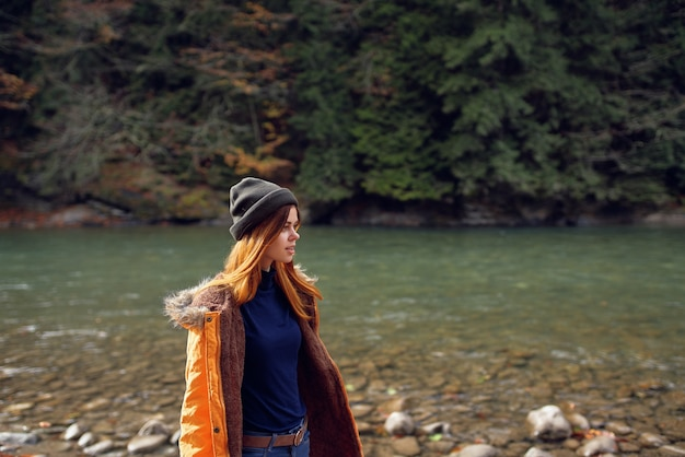 Woman tourists yellow jacket nature river travel autumn