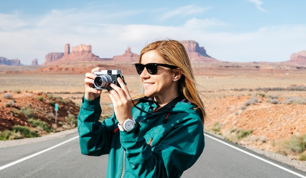 A woman tours take a photo with camera at the famous monument valley desert highway in utah, usa.