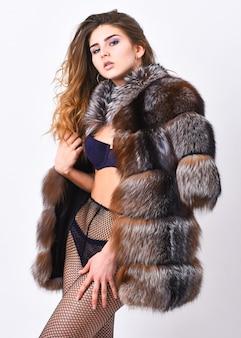 검은 란제리와 모피 재킷을 입고 포즈를 취한 여자 헝클어진 헤어스타일. 소녀 유혹자는 스타킹과 모피 코트를 입는다. 란제리 부티크 개념입니다. 여성용 속옷 란제리. 관능적인 소녀를 위한 엘리트 란제리.
