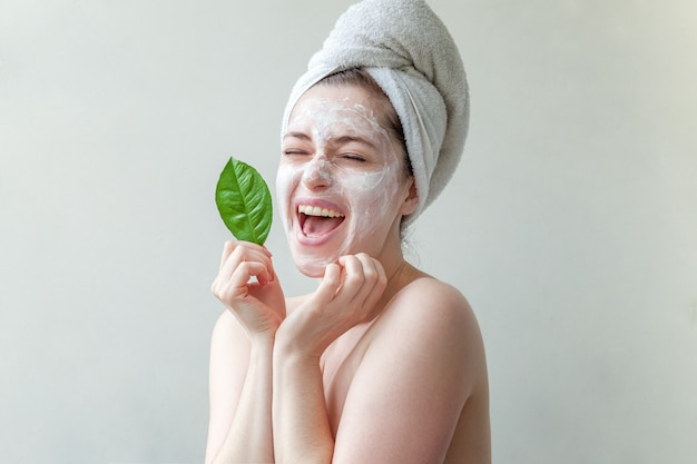 Woman in towel on head with white nourishing mask or creme on face and green leaf in hand