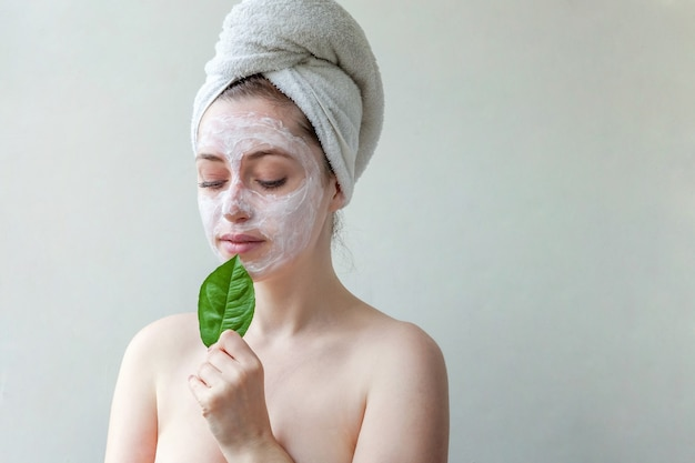 Woman in towel on head with white nourishing mask or creme on face, white background