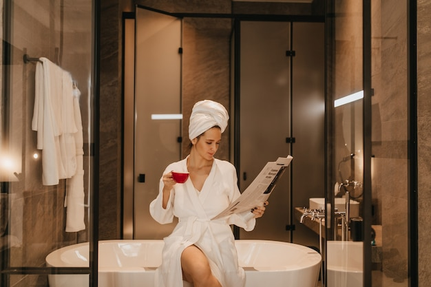 Woman in towel on her head and bathrobe reads latest news. lady with cup of tea posing in bathroom.