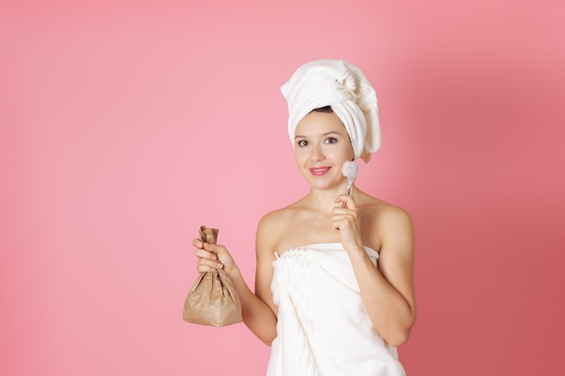 Woman in towel holding scrub in paper bag and glass face brush cleansing process