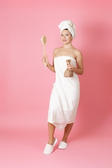 Woman in a towel holds a scrub in a paper bag and a wooden brush for anti cellulite massage