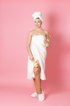 Woman in a towel holds a scruband massages her leg with a wooden brush