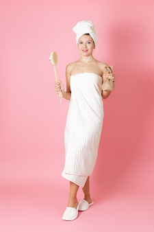 Woman in a towel holds a wooden brush for anticellulite massage and scrub