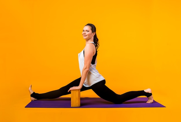 A woman in a tracksuit performs yoga exercises with bricks on a purple mat on an orange wall