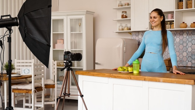A woman in a tracksuit records a video blog about sports and healthy eating. professional equipment in the photo studio with kitchen interior