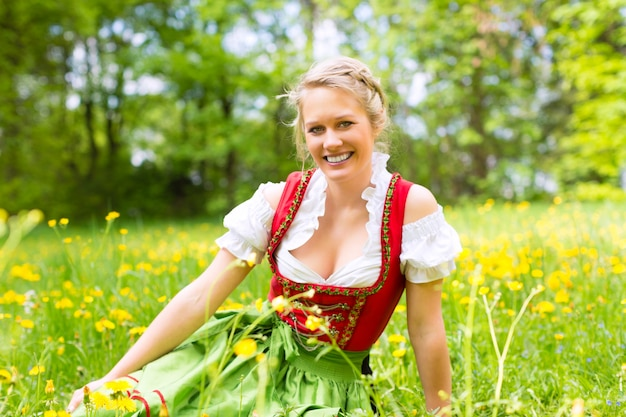 Woman in traditional bavarian clothes or dirndl on a meadow
