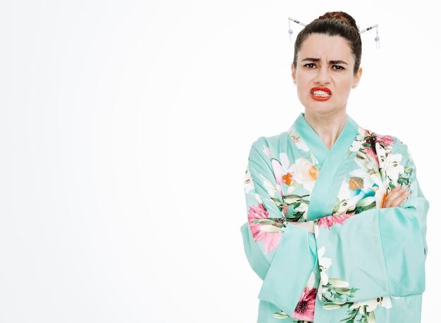 Donna in kimono tradizionale giapponese infastidita e insoddisfatta che fa la bocca storta che mostra i denti su bianco