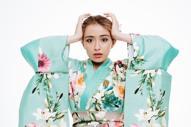 Donna in kimono tradizionale giapponese confusa e delusa che si tiene per mano sulla testa su bianco