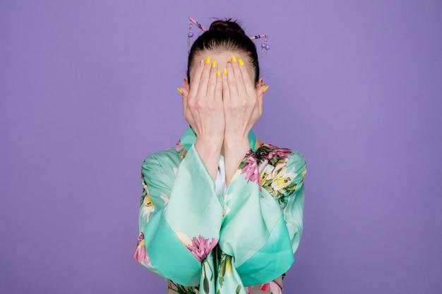 Donna in kimono tradizionale giapponese con la faccia con le mani sul viola