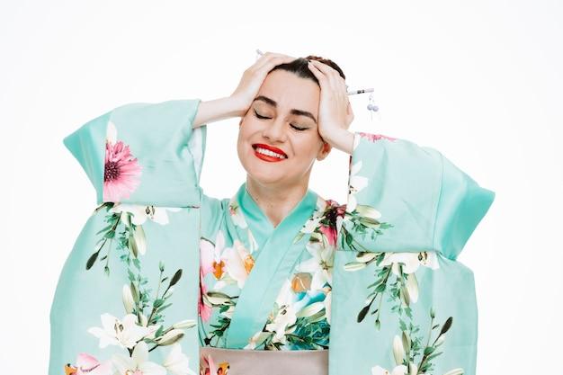 Donna in kimono tradizionale giapponese felice e contenta che si sente adorabile tenendosi per mano sulla testa su bianco