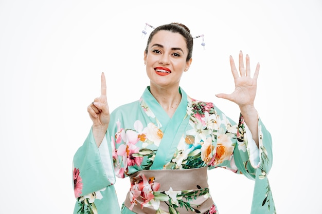 Woman in traditional japanese kimono happy and positive showing number six with fingers on white