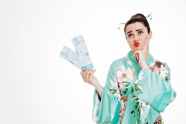 Donna in kimono tradizionale giapponese che tiene biglietti aerei guardando in alto con espressione pensierosa che tiene la mano sul mento su bianco