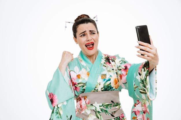 Donna in kimono giapponese tradizionale che tiene il pugno serrato dello smartphone esultando per il suo successo pazzo felice ed eccitato su bianco