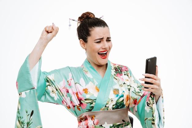Donna in kimono giapponese tradizionale che tiene il pugno serrato dello smartphone esultando per il suo successo felice ed eccitata su bianco