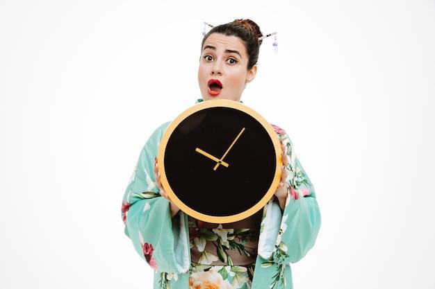Donna in kimono tradizionale giapponese con orologio da parete stupito e sorpreso su bianco