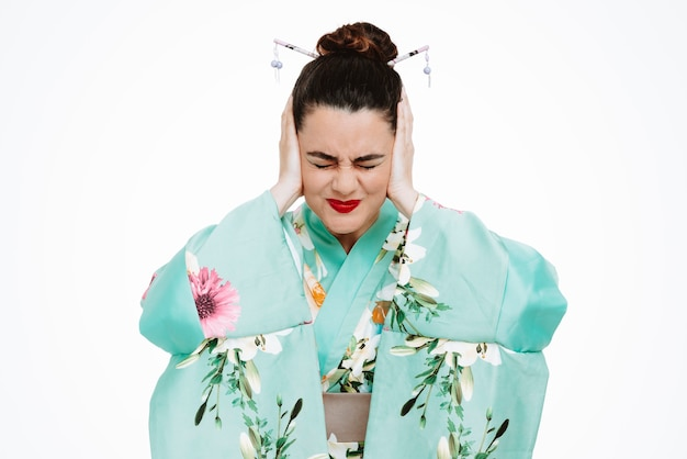 Woman in traditional japanese kimono looking annoyed closing eras with hands suffering from noise on white