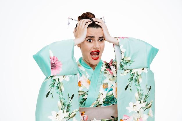 Donna in kimono tradizionale giapponese che guarda da parte stressata e scioccata tenendosi per mano sulla testa gridando su bianco