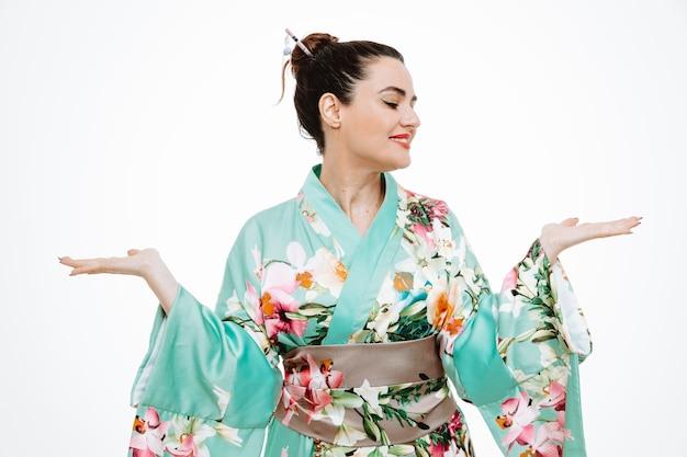 Donna in kimono giapponese tradizionale che guarda da parte presentando qualcosa con le braccia delle mani su bianco