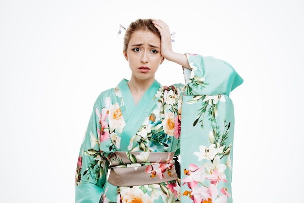 Donna in kimono tradizionale giapponese che sembra confusa e preoccupata che tiene la mano sulla testa per errore su bianco