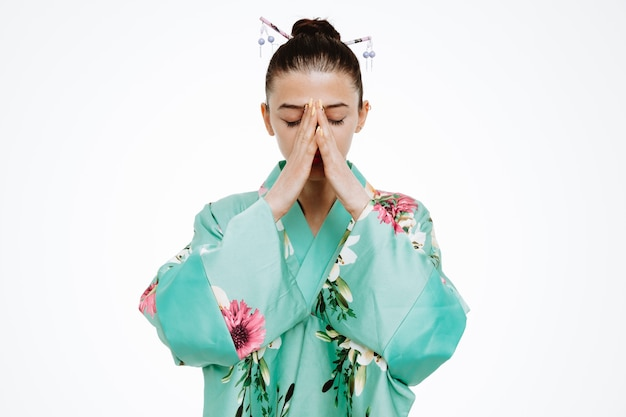Donna in kimono giapponese tradizionale che sembra triste che tiene insieme gli abbigliamenti su bianco