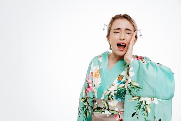 Donna in kimono tradizionale giapponese che sembra indisposta urlando toccandosi la guancia sentendo dolore con mal di denti su bianco
