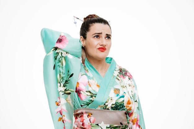 Donna in kimono tradizionale giapponese che sembra indisposta toccandosi il collo sentendo dolore su bianco