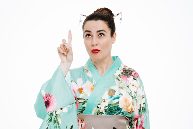Woman in traditional japanese kimono looking up pointing with index finger up having doubts being confused on white