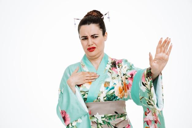Donna in kimono giapponese tradizionale che guarda con un'espressione disgustata che fa un gesto di arresto alzando le mani su bianco