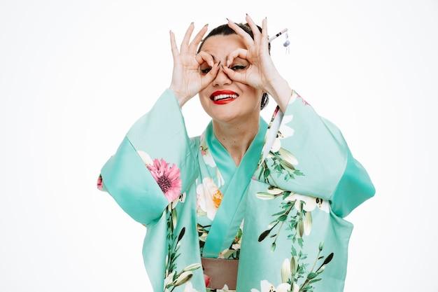 Donna in kimono tradizionale giapponese che fa un gesto binoculare attraverso le dita felice e allegro che sorride ampiamente su bianco