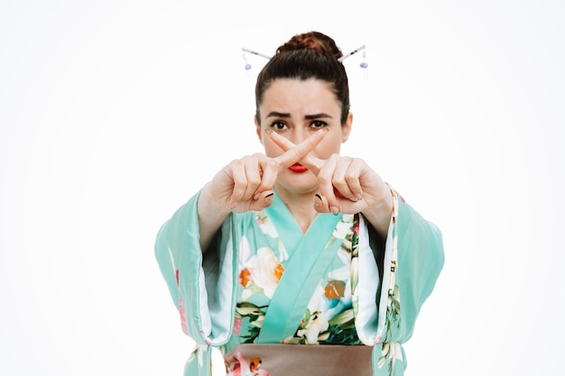Woman in traditional japanese kimono with serious face making stop gesture crossing index fingers on white