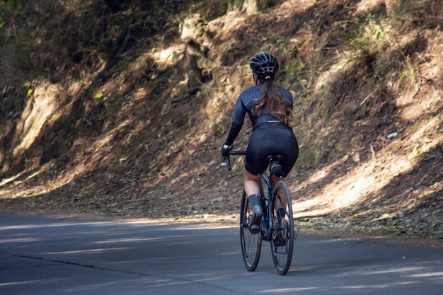 Woman on trail bike on a road in the middle of the forest outdoor sport concept