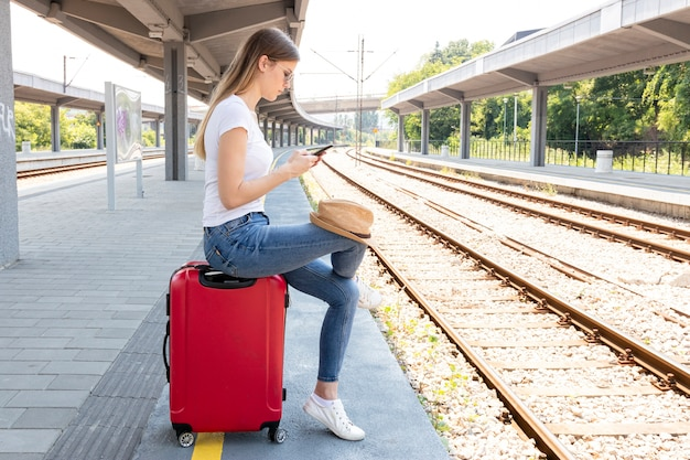 Woman in a train station sitting on a luggage
