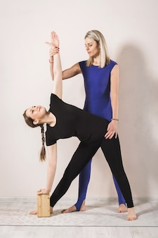 Woman trainer practicing yoga shows how to correctly perform the extended triangle exercise for a student a woman in black sportswear stands in the utthita trikonasana pose on the mat