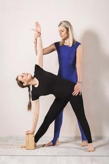 Женщина-тренер, практикующая йогу, показывает, как правильно выполнять упражнение расширенного треугольника для ученицы. женщина в черной спортивной одежде стоит на коврике в позе уттхита триконасана.