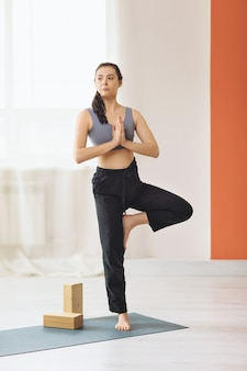 Woman trainer practicing yoga standing on a mat in the studio near the window performs vrikshasana exercise tree pose with namaste