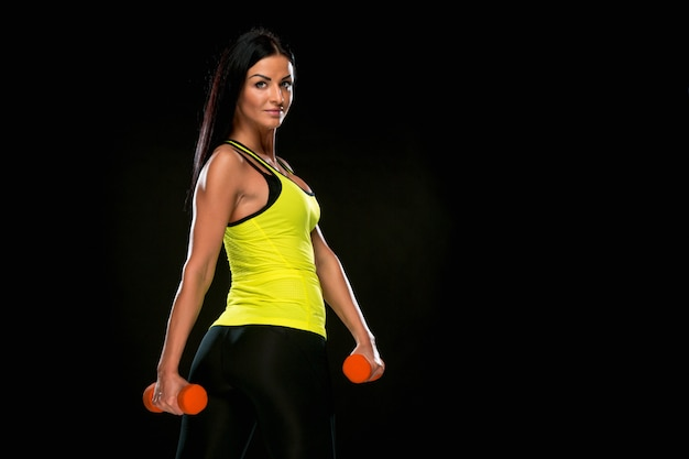 The woman training against black studio with red dumbbells
