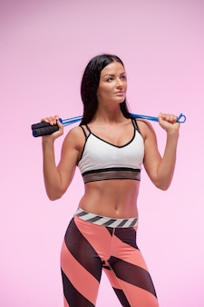 The woman training against pink studio with jump rope