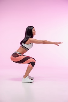 The woman training against pink studio