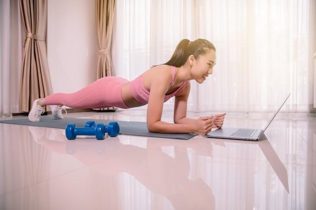 Женщина тренируется дома, делает планку и смотрит видео на ноутбуке