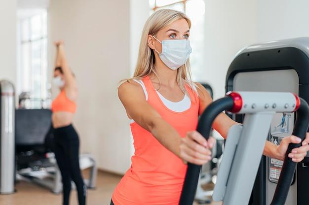 마스크와 체육관에서 훈련하는 여자