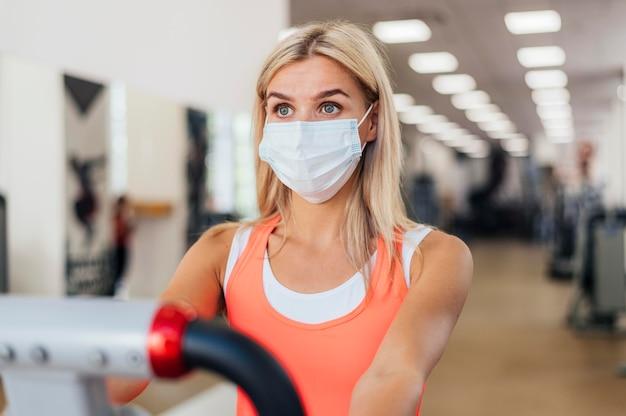 Женщина тренируется в тренажерном зале с медицинской маской