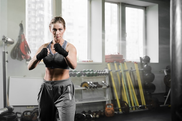 Woman training in boxing training center with copy space