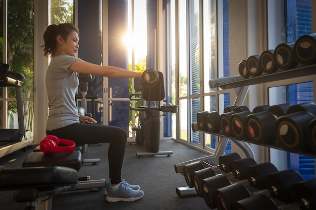 Woman training by lifting barbell