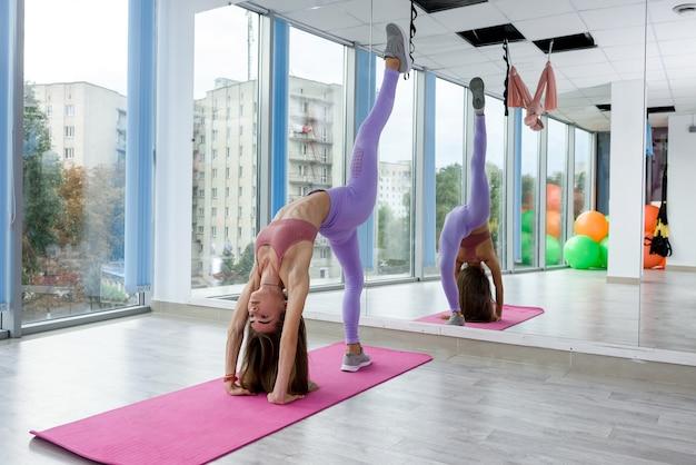 激しい仕事の前にスタジオで健康的なライフスタイルのためにストレッチするフィットネストレーニングをトレーニングする女性。女性アスリート