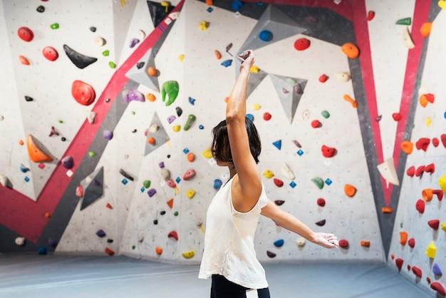 屋内の人工壁でロッククライミングを練習するための女性のトレーニング。アクティブなライフスタイルとボルダリングのコンセプト。