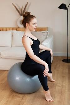 Woman training on gym ball full shot